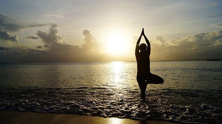 Der Baum am Strand – Yogaübung für Einsteiger am Rand des Ozeans bei Sonnenaufgang.