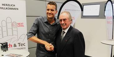 Albert Busek und Ironman-Weltmeister Jan Frodeno beim Aufstiegskongress 2019